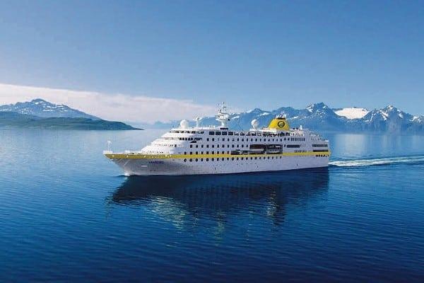 Das Expeditionsschiff MS Hamburg unterwegs im Meer, zwischen Bergen