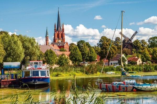 Havelland mit grünem See, Schiffen und einer roten Kirche im Hintergrund