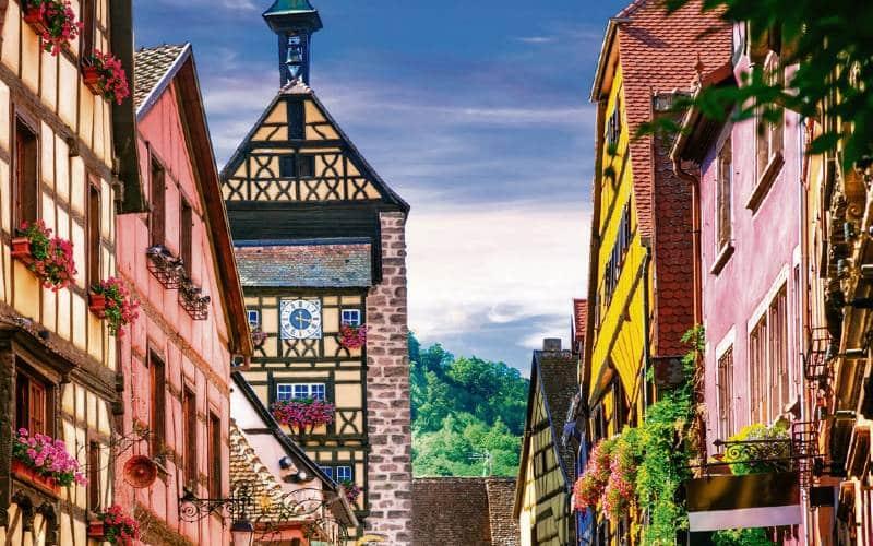 Eine Gasse In Der Altstadt Von Riquewihr Mit Farbigen Rigelhäusern