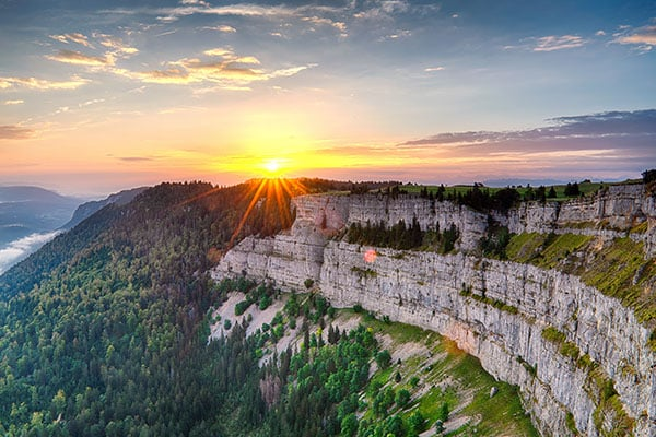 Vivid sunset with sunstar over cliff Creux du Van Neuchatel in w